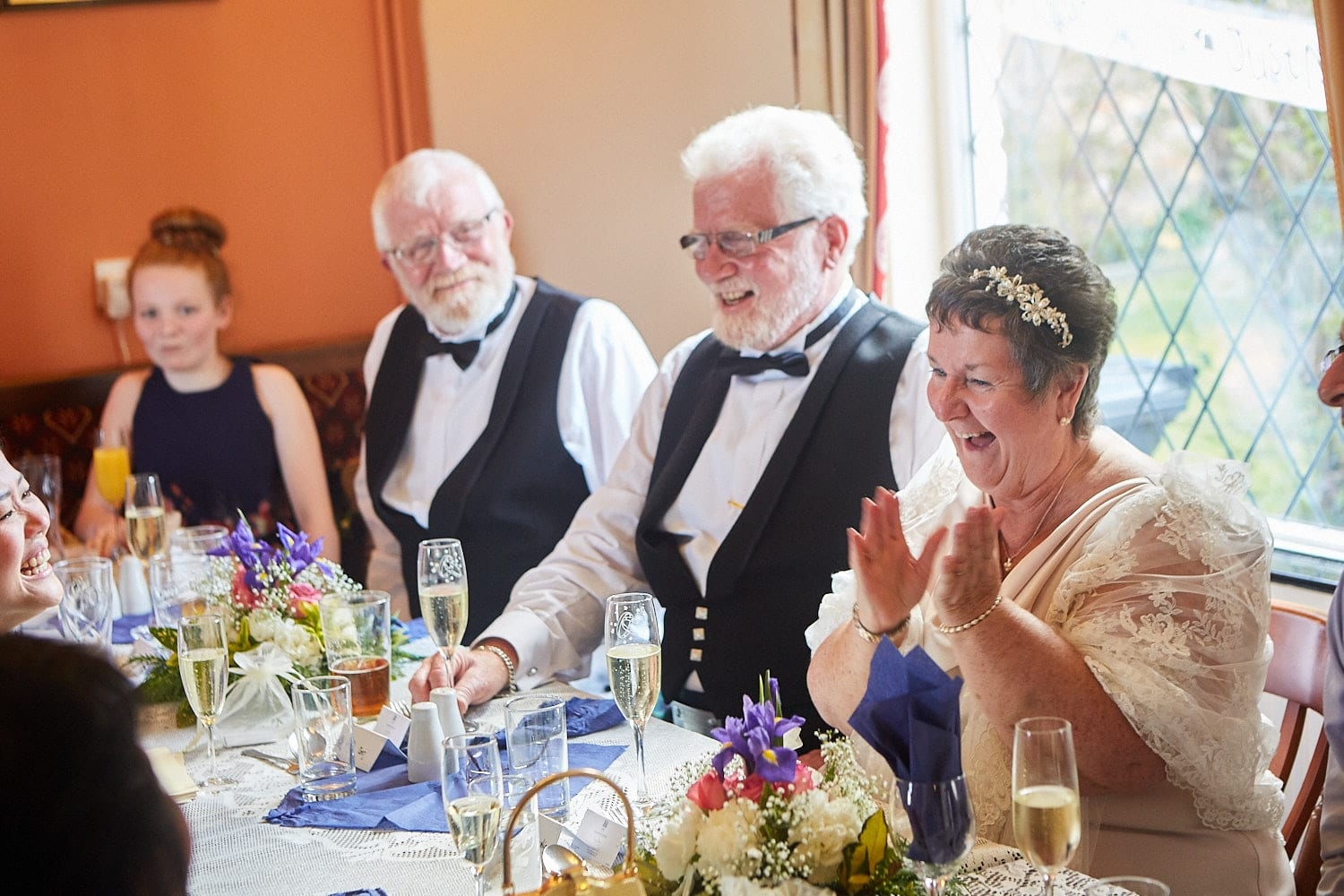 A bride, her husband and the best man laugh at speeches on their wedding day