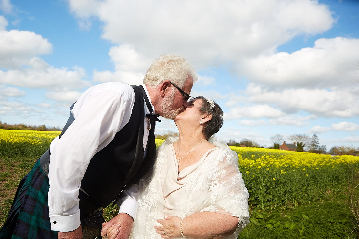 An older, just married couple kiss.