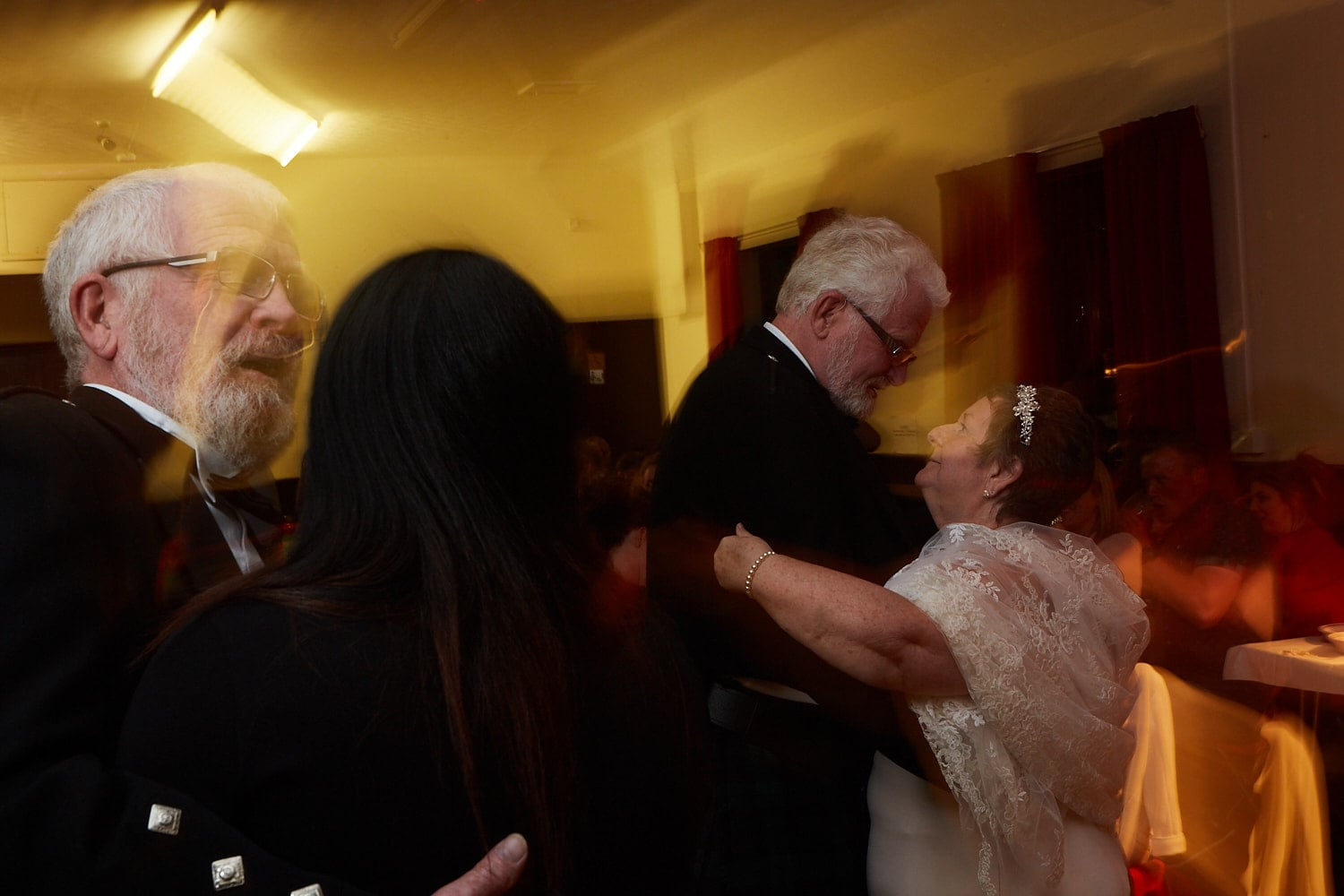 A bride & groom along with the best man and his granddaughter dance at a wedding reception