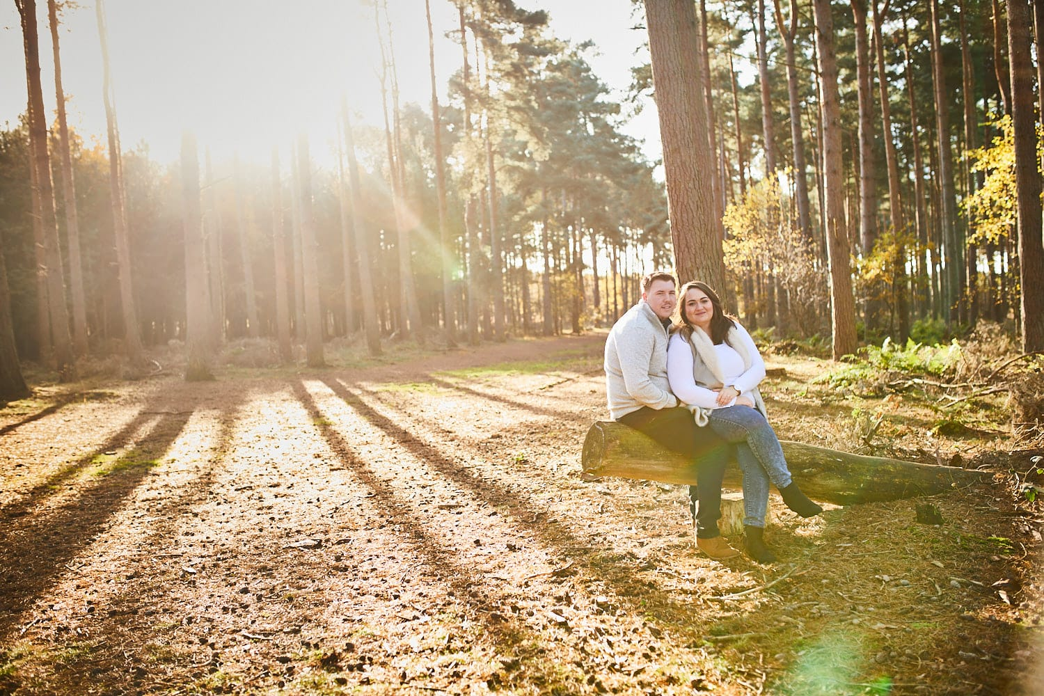 A couple sit together on a fallen log in Woodhall Spa Woodland Lincolnshire