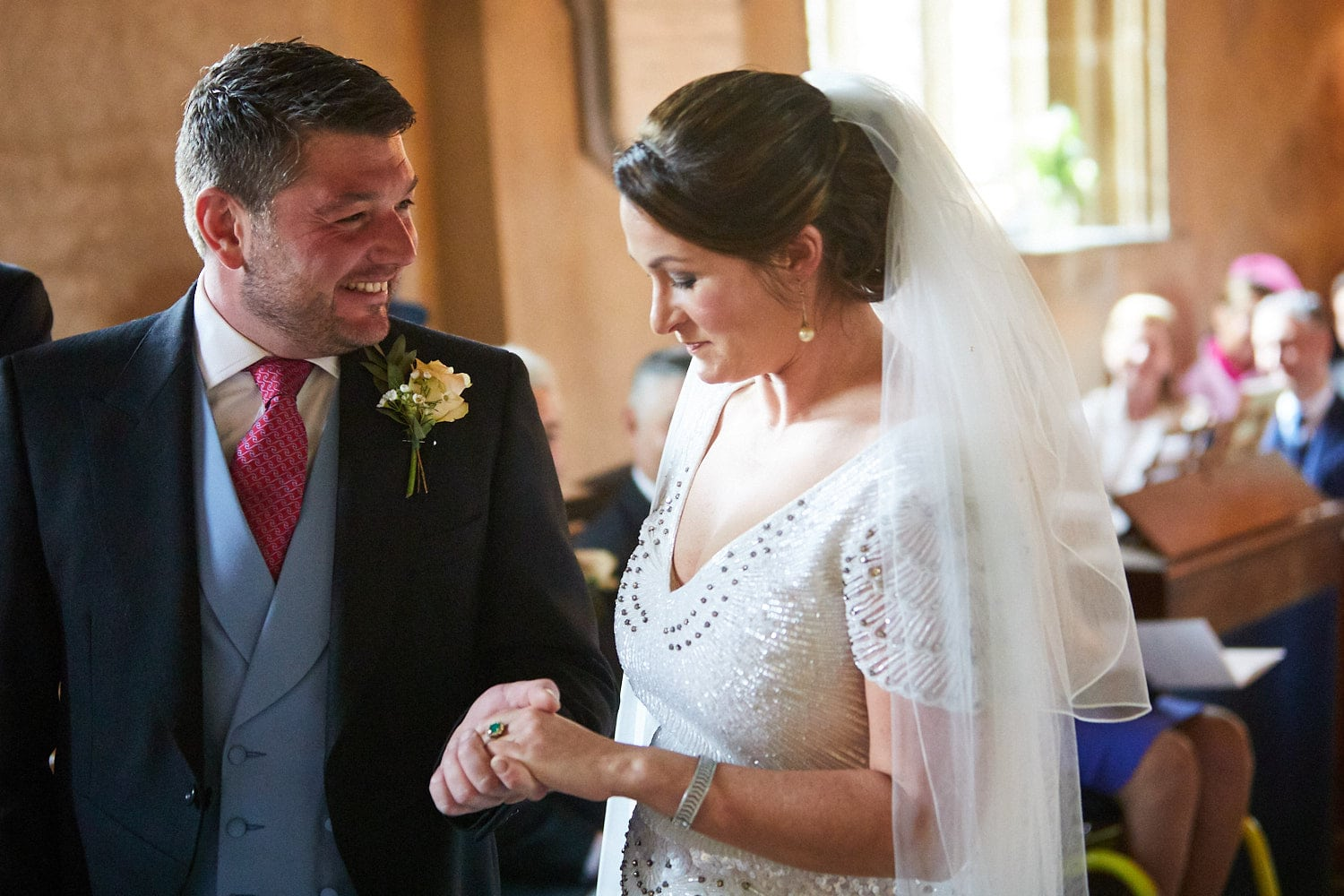 A groom smiles as he looks at his wife lovingly after they exchanged rings on their wedding day