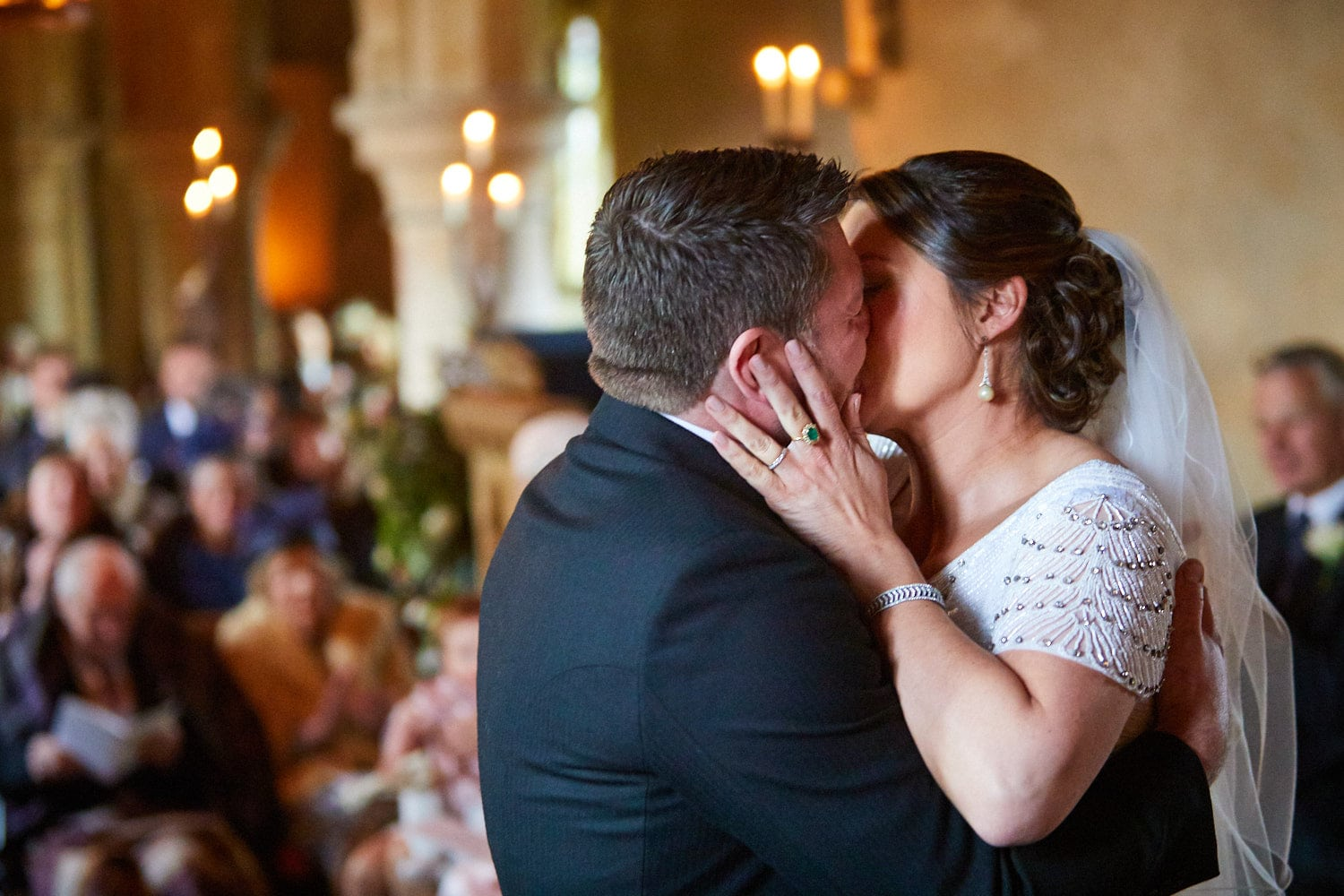 A bride and groom kiss on their wedding day at the Saxon church at Howell Manor, Sleaford.