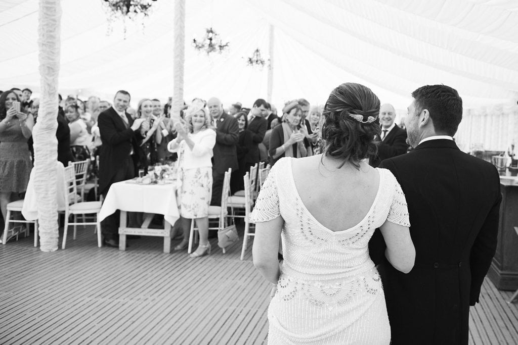 A couple enter their wedding marquee to greet their guests, who are standing an applauding at a Marquee wedding in Heckington, Lincolnshire.