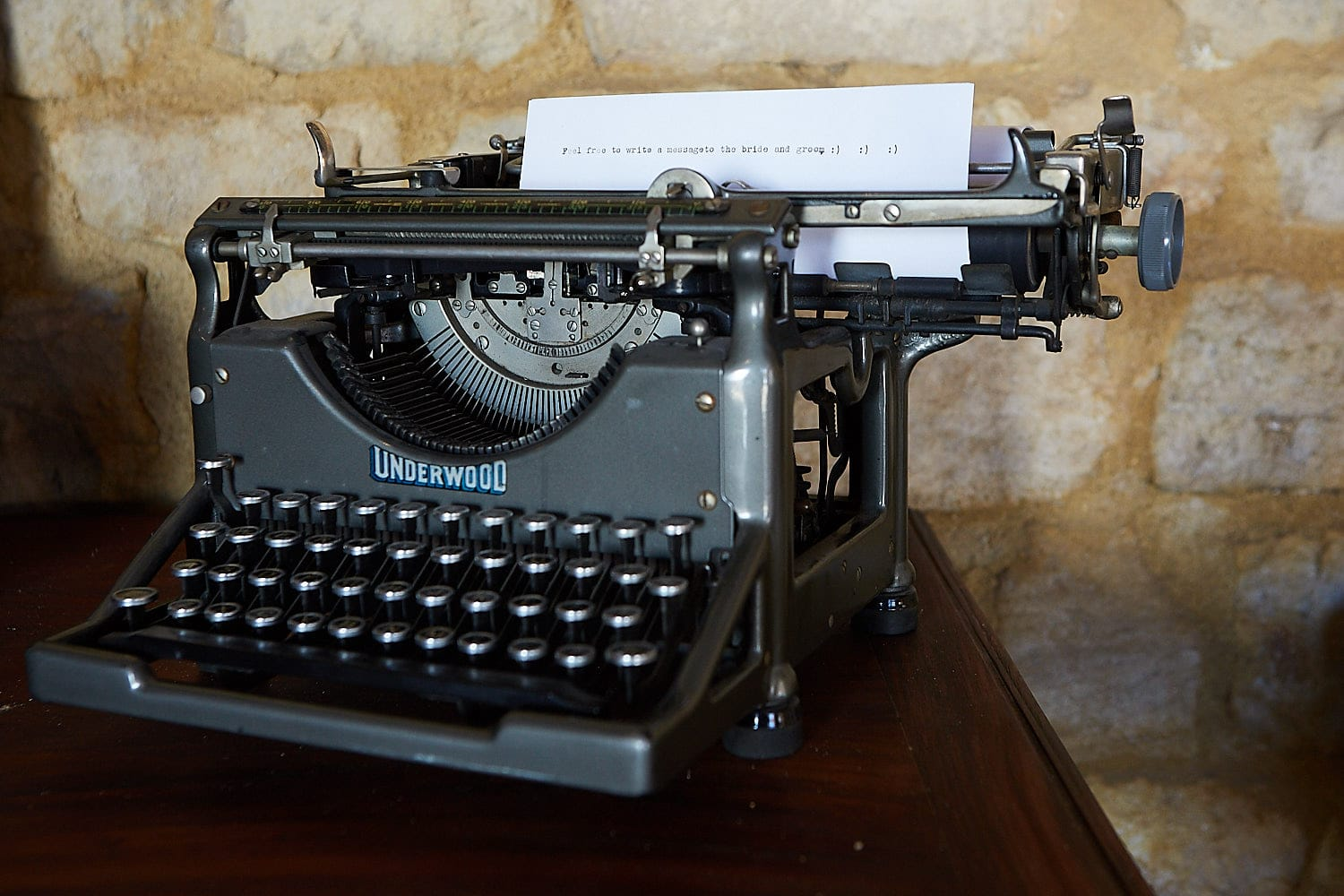 "A typewriter sits at a wedding with instructions for guests to type their messages onto it. It reads ""feel free to write a message to the bride and groom"""