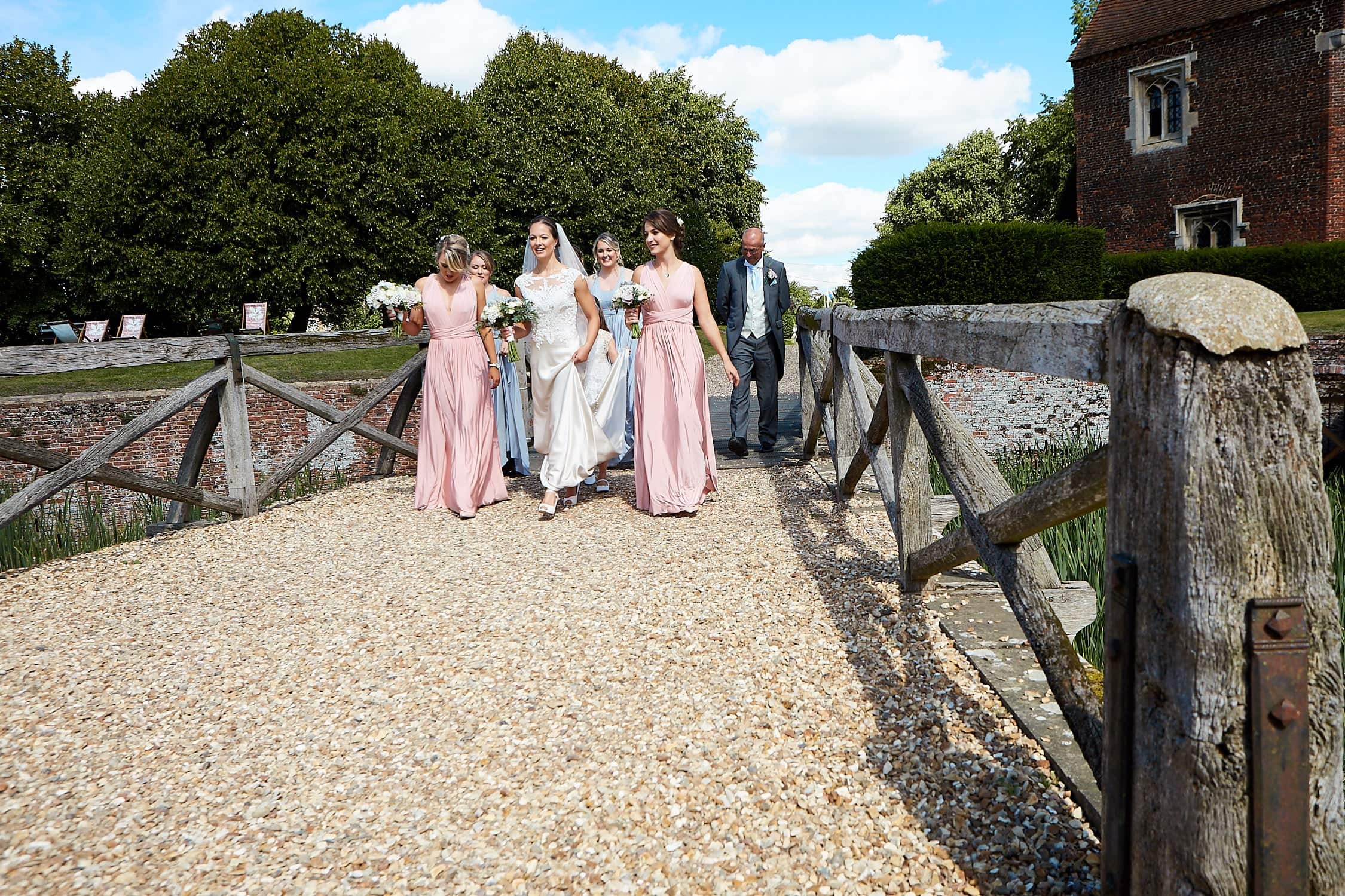 A bride and her bridesmaids walk towards Tattershall Castle