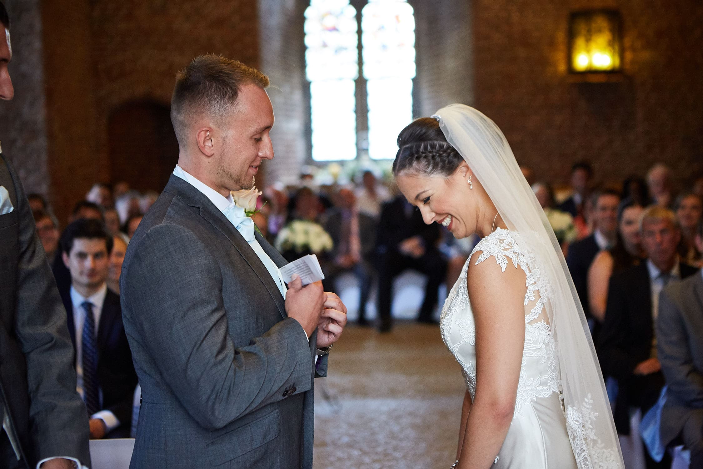 A groom pulls out his vows whilst his bride laughs