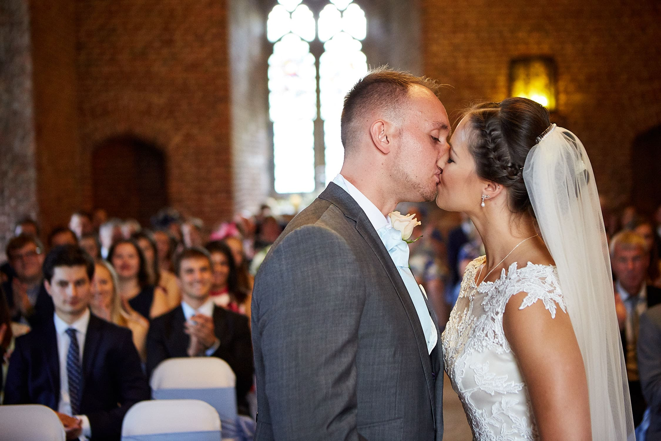 A groom kisses his new wife during their ceremony at Tattershall Castle National Trust Wedding venue.