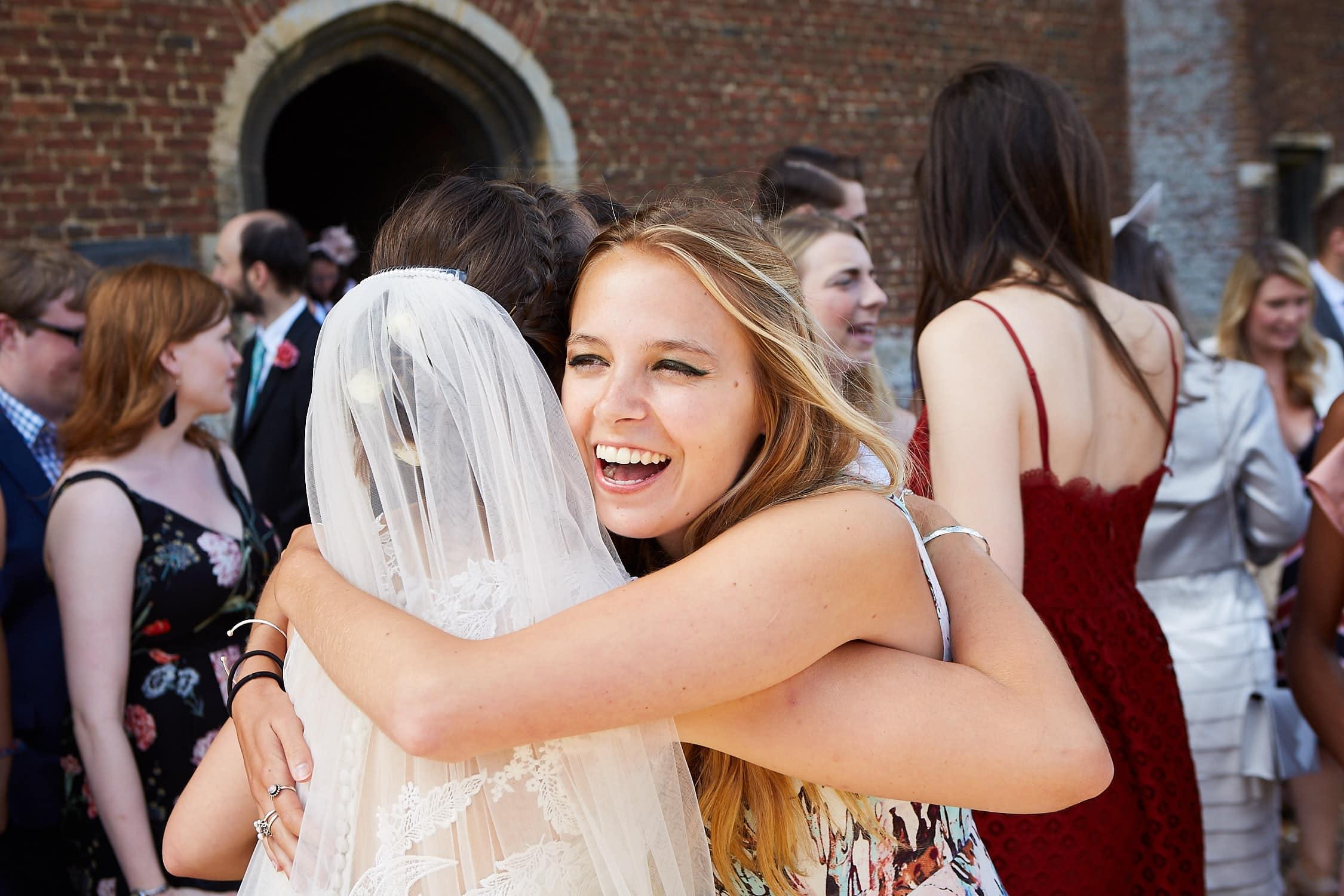 Hugging a bride a guest smiles