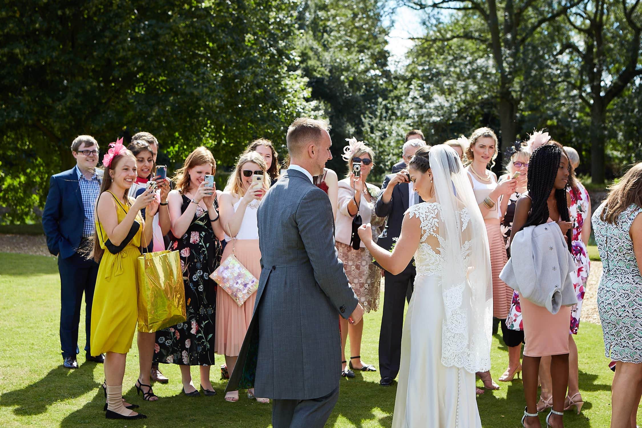Bride and groom face friends as they photograph their wedding day