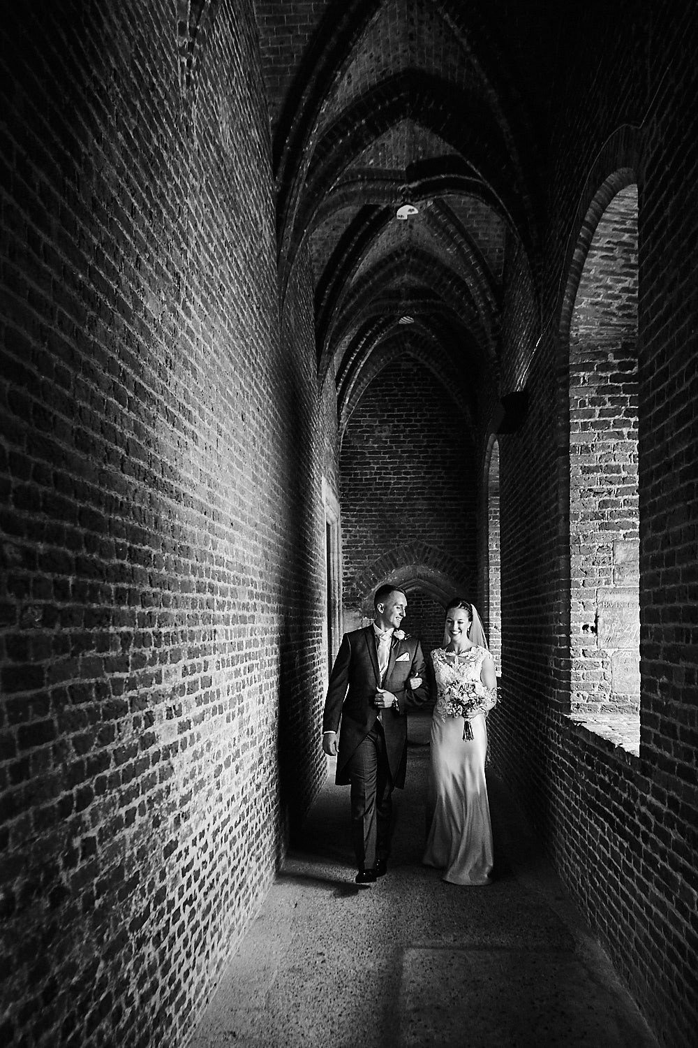 Birde & Groom walking in Tattershall Castle building