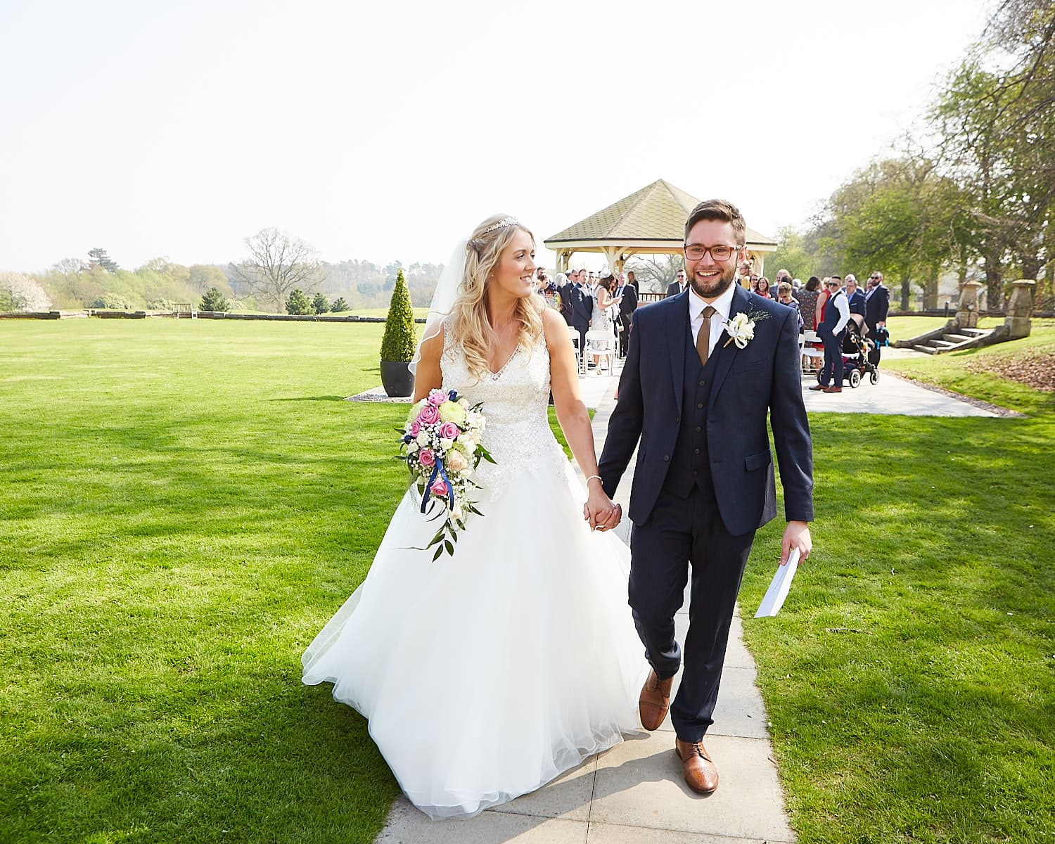 A newly married couple walking together outdoors at Kenwick Park Hotel Louth