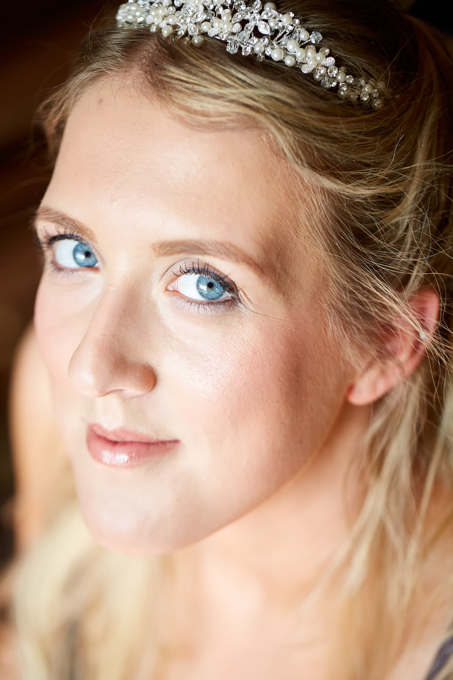 bride looks into camera after her wedding makeup is completed