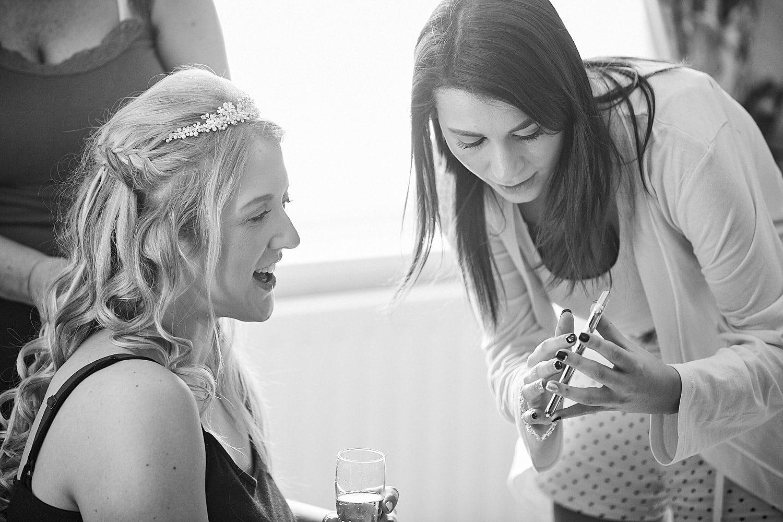 A bridesmaid and bride look into a phone during bridal preparations