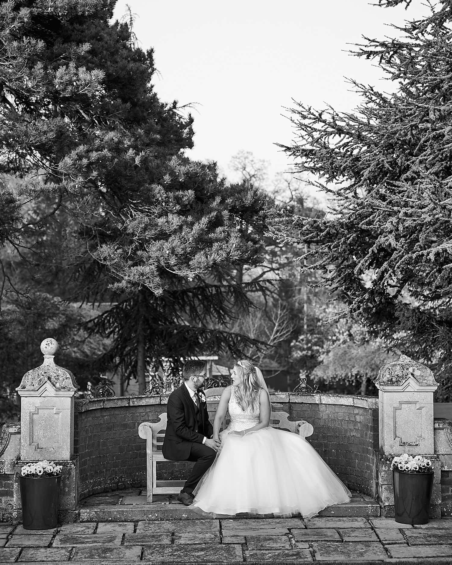 A couple chat on a bench during their wedding day.