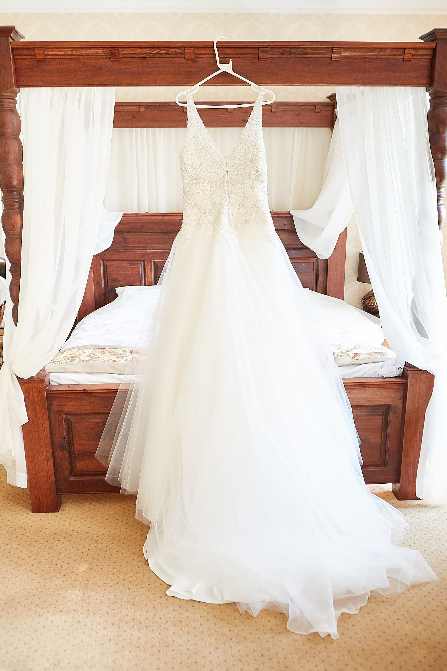 A dress hanging from a four poster bed