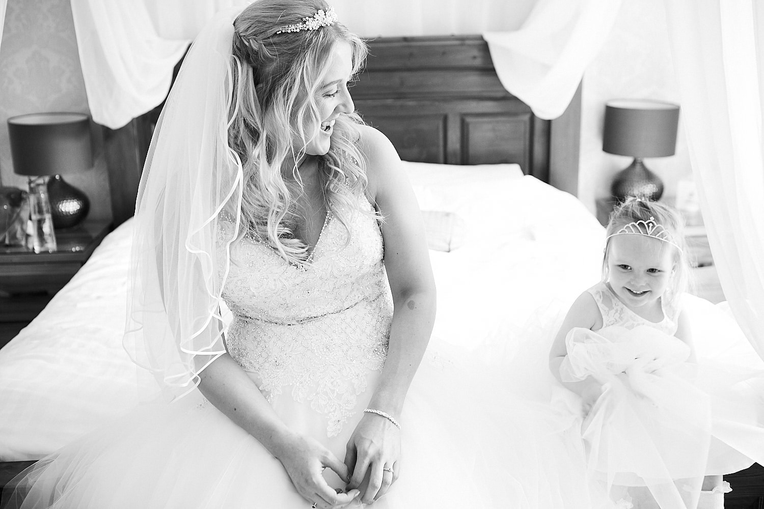 A bride and her flower girl sit on the bed