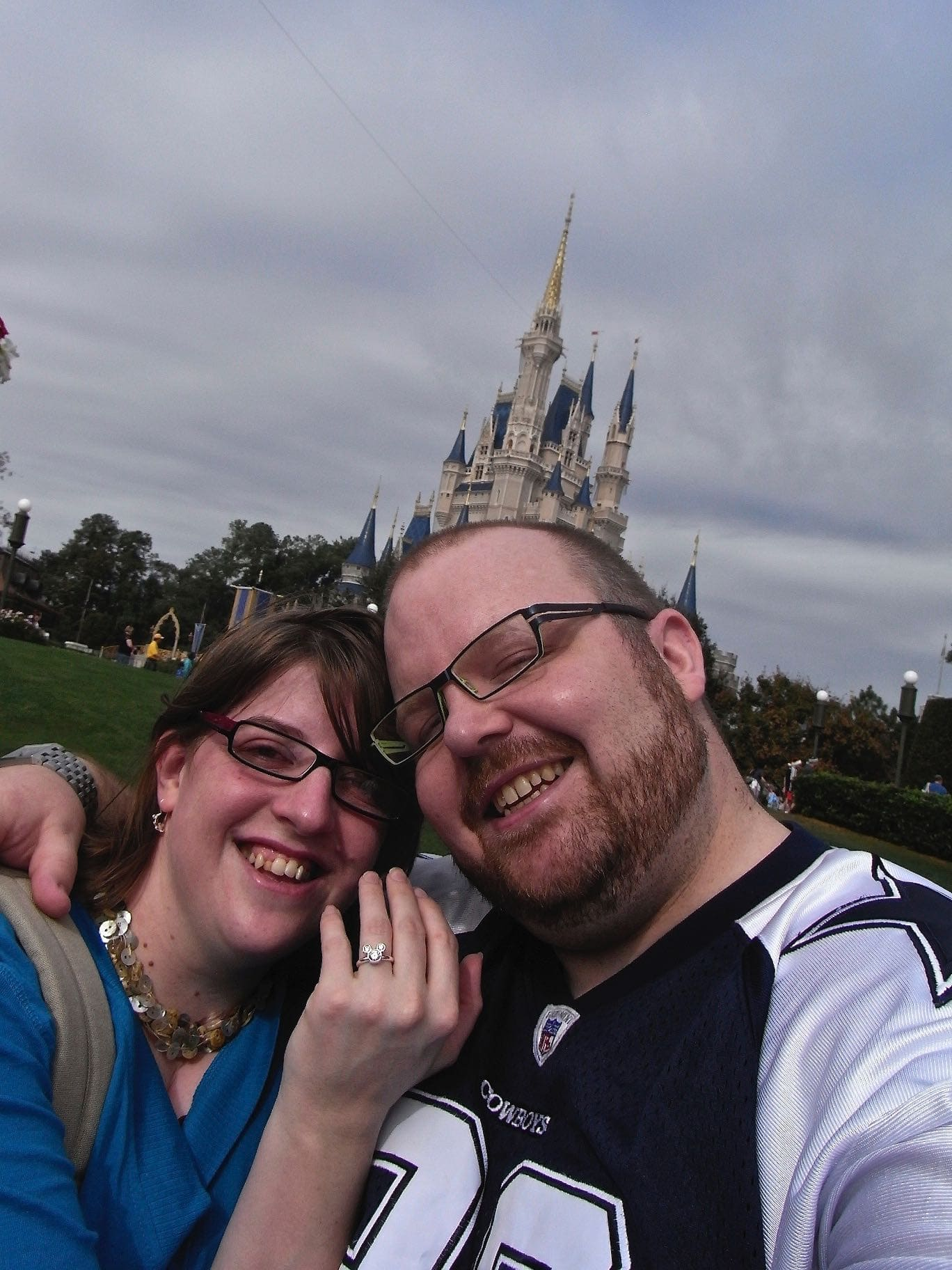 A selfie of a couple in front of Cinderellas castle in Disney where he has just proposed